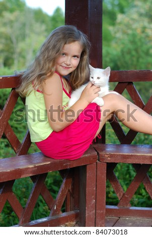 The little girl with a white kitten on a bench - stock photo