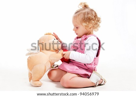 The little girl with blond hair in a pink dress playing with a doll