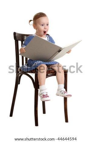 The little girl with enthusiasm reads the book sitting on a chair - stock photo
