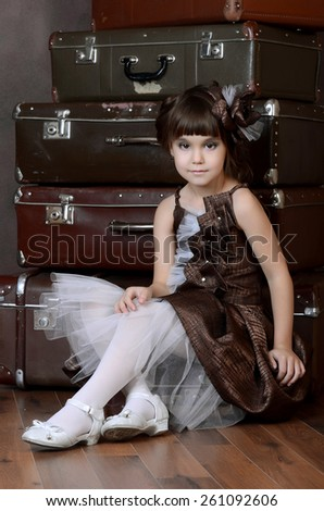 The little girl with old retro suitcases - stock photo