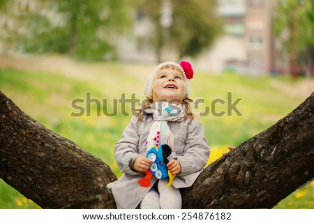 The little lovely amusing delightful girl sitting on the blossoming tree watches a look up. On warm sunny spring day. - stock photo