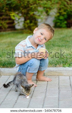 The little nice boy with ice-cream in park - stock photo
