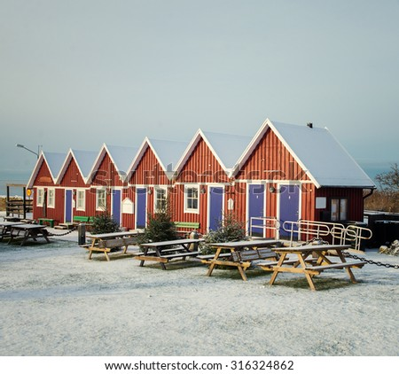 the little red house by the sea - stock photo