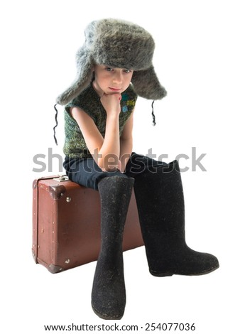 The little Russian boy in a fur hat and boots sitting on old suitcase and thinking on a white background
