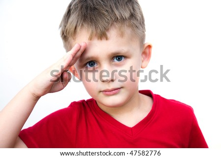 The little smiling boy saluting as soldiers - stock photo