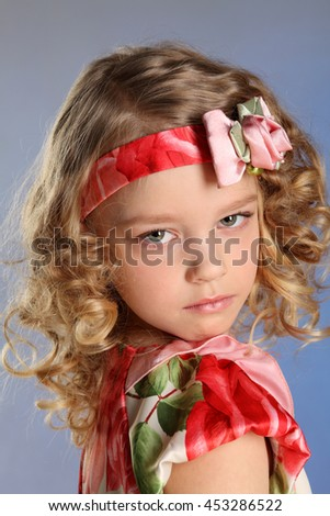 The little spruced girl with blond curly hair. Close-up portrait. The child is upset.
