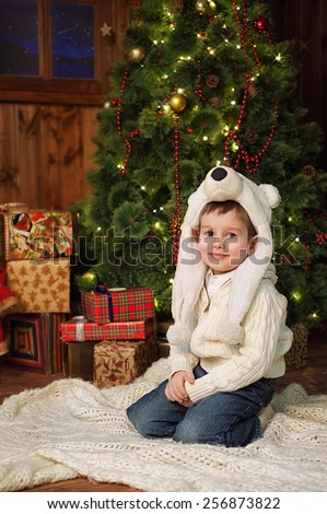 the little 4years boy sitting near a Christmas tree in a wooden country style house. - stock photo