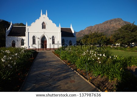 The local church is a great example of Colonial architecture from it's dutch decent in Franschhoek, Western Cape, South Africa. - stock photo