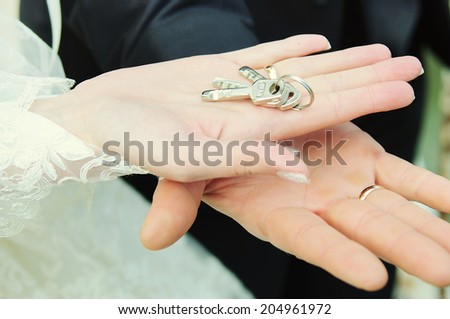 The lock with keys in hands of the groom and the bride - stock photo