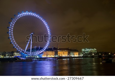 The London Eye on the shores of the river Thames at night - stock photo