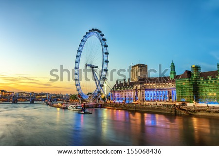 The London Eye on the South Bank of the River Thames at night in London, England. - stock photo