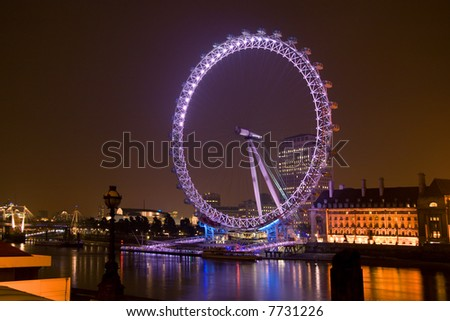 The London Eye overlooking the Thames at night - stock photo