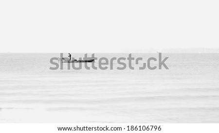 The lone fisherman ,fisherman boat,fisherman in sea monochrome,black and white  - stock photo