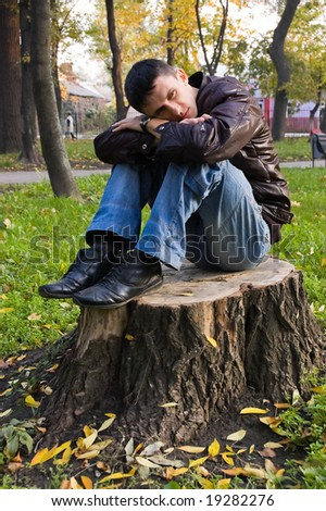 The lonely guy sits on a stub, thinking about something - stock photo