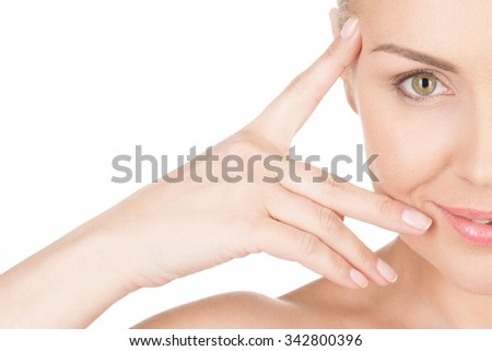 The look of mature. Horizontal cropped shot of a gorgeous woman smiling warmly and touching her face - stock photo