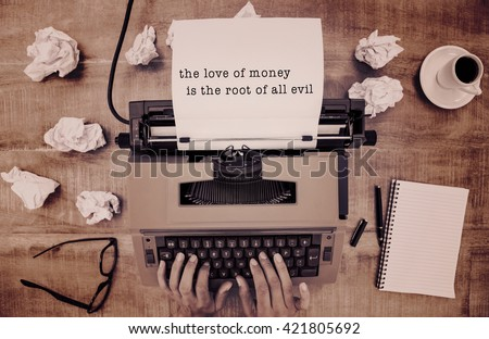 The love of money is the root of all evil message on a white background against above view of old typewriter - stock photo