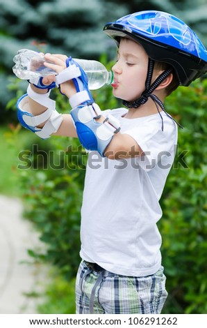 the lovely boy skater drinking water from a bottle - stock photo