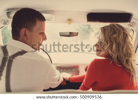 The lovely couple in love hold hands in car