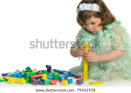 The lovely little girl plays colour wooden cubes. It is isolated on a white background