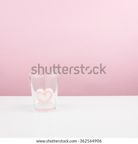 The lovely pink heart marshmallow in shot glass on white table. - stock photo
