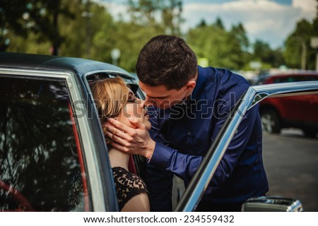 the loving couple kisses at the car - stock photo