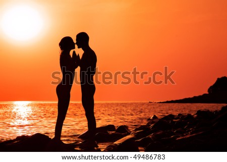 The loving couple on a decline, the sea, shines the sun