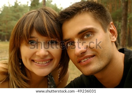 The loving couple poses against forest