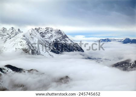 The low clouds over high mountains at winter day - stock photo