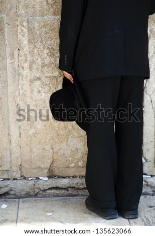 The lower body part of an orthodox Jewish young adult holding his hat and praying at the wailing wall in the old city of Jerusalem. - stock photo