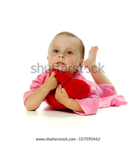 The lying baby embraces heart on a white background.