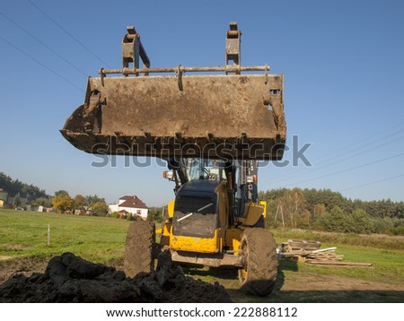 The machine, wheel loader during backfilling around the foundation of the building on the site - stock photo