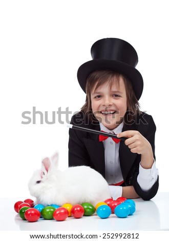 The magic of easter - happy magician boy conjuring a grumpy rabbit and colorful eggs, isolated - stock photo
