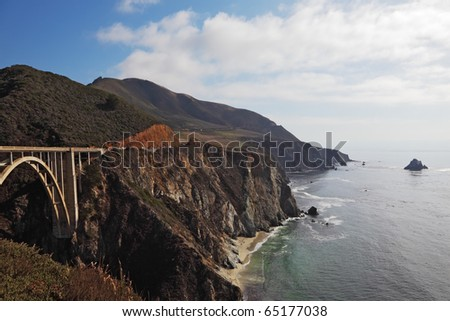 The magnificent bridge on a coastal motorway of rocky and steep Pacific coast USA - stock photo