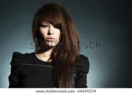 The magnificent young woman in a black dress on a dark background. - stock photo