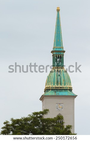 The main cathedral tower in Bratislava, Slovakia. Green roof with golden elements against a bright summer foliage - stock photo