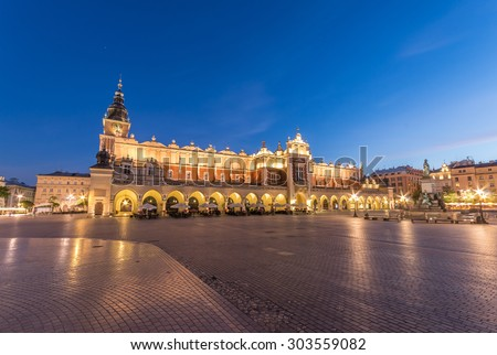 The Main Market Square in Krakow, Poland, with famous Sukiennice (Cloth hall) and Town Hall tower in blue hour - stock photo