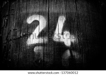the main number is twenty four painted on wood in black and white - stock photo