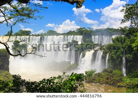 The majestic Iguazu Falls,  on the background of blue sky, one of the wonders of the world
