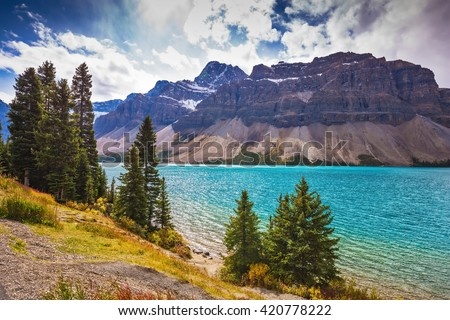 The majestic mountain glacial Bow Lake with green water. The lake is surrounded by pine trees. Banff National Park in the Canadian Rockies - stock photo