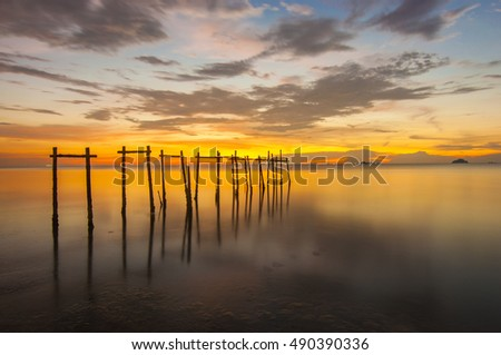 the majestic sunrise at the jetty. nature composition and soft focus. slow shutter speed set up caused the motion to the cloud and water.