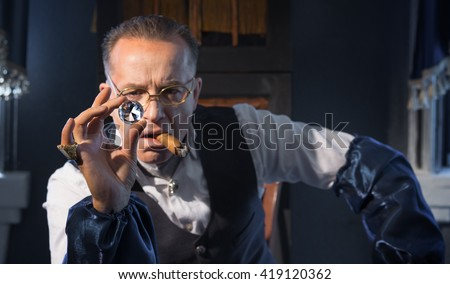 The man - a jeweler examines jewelry - stock photo