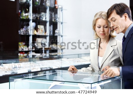 The man and the woman aged choose an accessory - stock photo