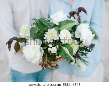 the man and woman dressed in light clothes stand nearby and hold in hand beautiful flower composition from white colors outdoors.