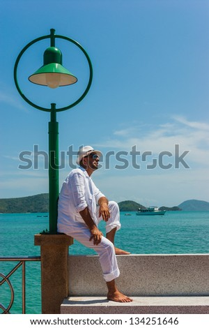 The man at the resort in a white suit and hat sitting on a rock on the sea background