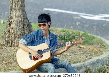 The man can play the acoustic guitar in happiness. (portrait solf pictue subject at the man and blurry background )