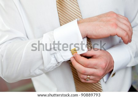 The man clasps a cuff link on a shirt - stock photo