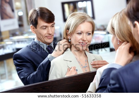 The man clasps a jeweller necklace to the woman - stock photo