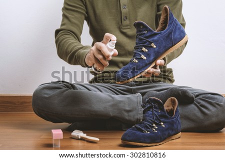 The man cleaning his suede shoes - stock photo