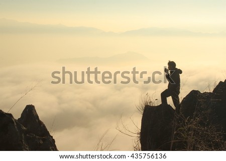The Man drinking coffee on the mountain in fog .low key lighting .Silhouette .Selective focus