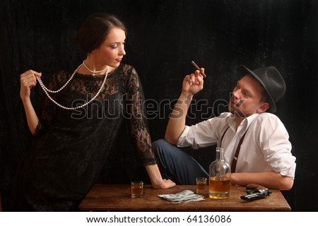 The man-gangster and the beautiful girl talk in a bar - stock photo